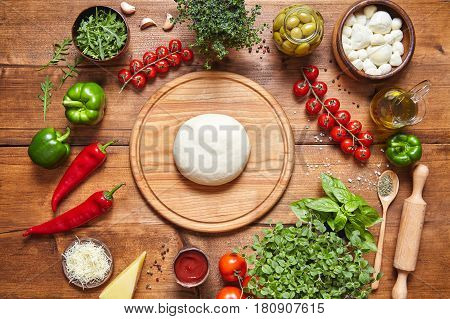 Italian food cuisine background. Pizza cooking ingredients: dough, mozzarella, tomatoes, basil, olive oil, cheese, sauce, spices, regano parmesan pepper herbs served on rustic wooden table
