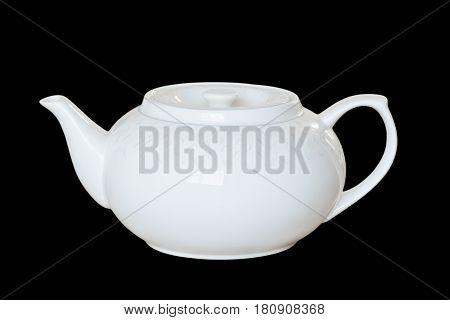 White porcelain teapot to brew tea or fragrant healing herbs. Isolated, black background.