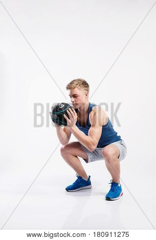 Handsome hipster fitness man in blue tank top shirt and gray shorts holding medicene ball, doing squat. Studio shot on gray background.