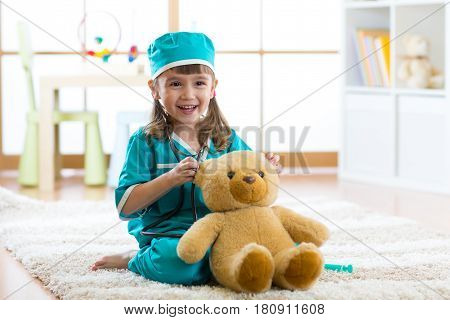 Cute child girl playing doctor with plush toy at home