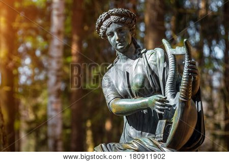 A Female Copper Statue Of A Deity With A Harp In The Woods