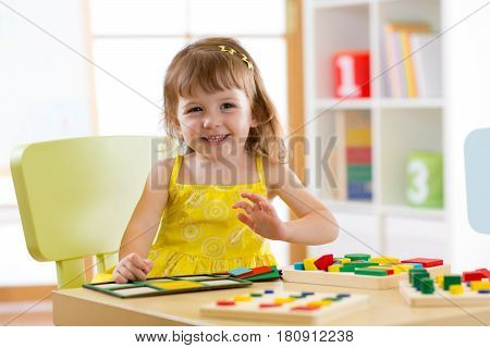 Child girl playing and learning colors shapes and sizes at table at home