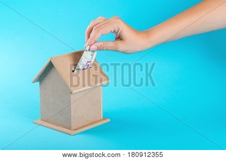 A female hand putting a five dollar into a money box. The concept of financial savings to buy the house.