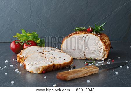 Roasted chicken breast for sandwiches with two cut pieces on a greay abstract background. Healthy eating concept. Selective focus