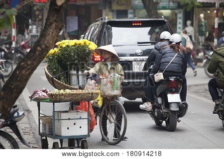 Hanoi, Vietnam - March 9, 2017: Woman selling flowers in the early morning in a busy street, Hanoi, Vietnam. Life of florist vendor in Hanoi, Vietnam.