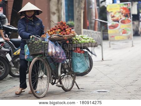 Hanoi, Vietnam - March 9, 2017: Woman selling fruits and vegetables in the early morning in a busy street, Hanoi, Vietnam. Life of avendor in Hanoi, Vietnam.