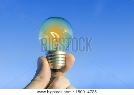 Concept idea of a burning incandescent lamp in a hand against a clear blue sky background from solar energy power