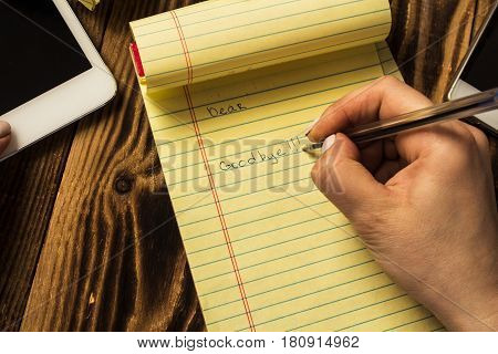 the woman's hand writing good bye in notebook