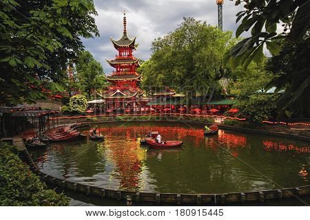 COPENHAGEN DENMARK - JUNE 15: Evening view of Tivoli Gardens with Chinese pagoda Dragon Boat lake and Daemonen roller coaster in 2012