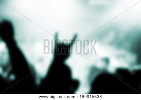 blurred silhouettes of people in a bright in the pop rock concert in front of the stage. Hands with gesture Horns. That rocks. Рarty in a club