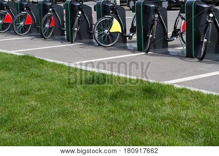 horizontal perspective view of city bike stand with row of bicycles for rent on a city park street with green grass in front