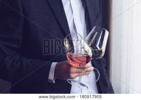 Horizontal close up of Caucasian man in black suit and white shirt holding two tall glasses with rose and white wine with one hand at an event by the window natural lighting