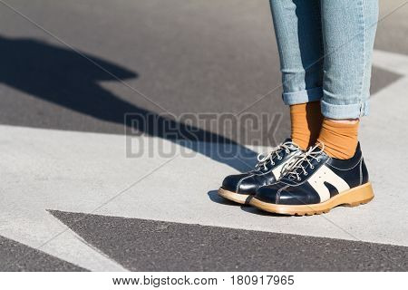 side view close up of a fashionable young woman wearing black shoes and blue jeans standing on a street natural light
