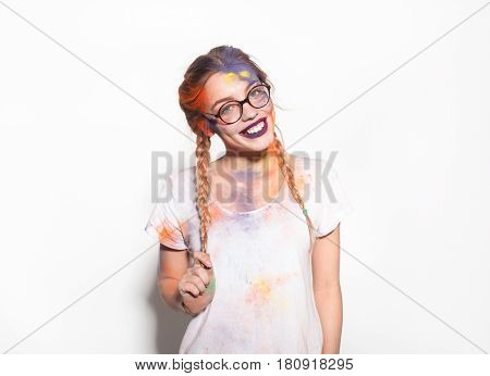 Lovely young girl in white t-shirt with face in dry colorful paints looking at camera on white.