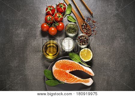 Raw steak of salmon with fresh ingredients on gray background.