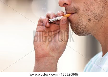 Smoking problem addiction to nicotine concept. Adult man in light shirt smoking cigarette outside.