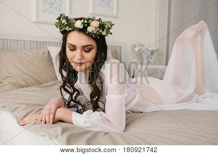 Young beautiful bride in a beautiful wedding dress with a wreath of flowers on her head lying in bed. Wedding. Bride's morning.