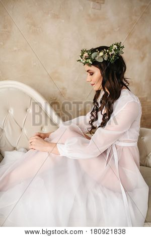 Young beautiful bride in a beautiful boudoir dress with a wreath of flowers on her head. Wedding. Bride's morning.