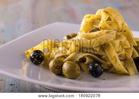 Portion Of Tagliatelle With Pesto And Capers And Olives