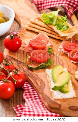 Crackers with ham and avocado on cutting board.