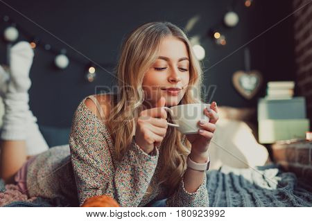 Cheerful young woman having a hot beverage on the bed. Horizontal indoors shot.