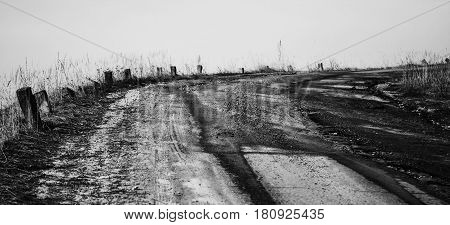 Black and white photography. The road is the concrete running upwards and the posts on the roadside.