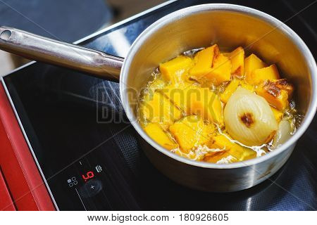 The process of making pumpkin soup - pumpkin sliced into pieces in a saucepan with onion and vegetables. Cooking vegetarian dishes in the kitchen - a pan with vegetables on the hob. Soft focus.