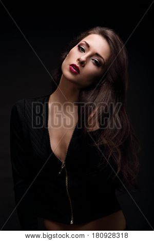 Sexy Makeup Woman With Red Lips In Jacket Posing In Dark Shadow Black Background. Closeup Portrait I