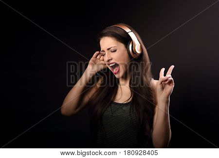 Beautiful Emotional Loudly Singing Woman Listening The Music In Wireless Headphone And Hand Showing
