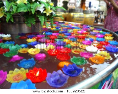 Blurred photo of flower floating candle lights vintage mode about Buddhism,Blurred photo can be background,flower candle floating on water.