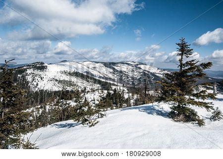 Malinowska skala Kopa Skrzyczenska Male Skrzyczne Skrzyczne and other hills on the background from Tielony Kopiec hill in winter Beskid Slaski mountaiins in Poland with snoad and blue sky with clouds