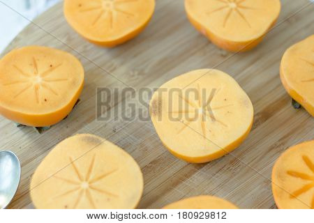 Persimmon Fruit Halves On Brown Wooden Board