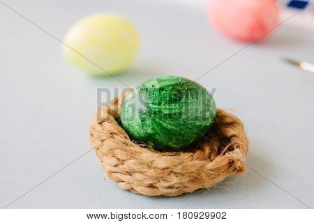 Green Color Easter Egg In Small Nest Over Bright Background