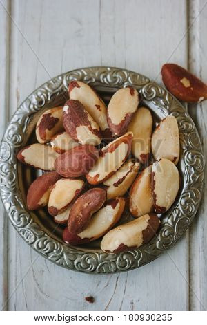 Brazil Nuts In Metal Plate Over The White Wooden Table.