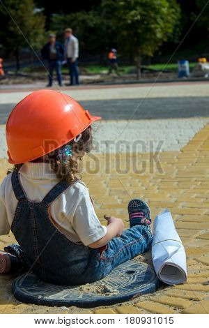 Little baby girl builder with the construction helmet and poster in denim uniform smiling on construction site
