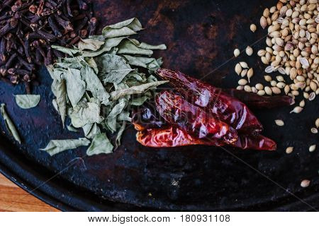 Green Curry Leaves On Black Metal Plate Surrounded By Other Spices.