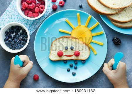 Creative idea for kid breakfast - sweet bread bun cloud with berry rain and fruit sun