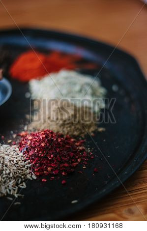 Red Sumac Spice On Black Metal Plate Surrounded By Other Spices.
