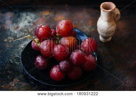 Small Clay Jug Behind The Grapes