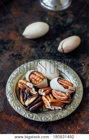 Pecan Nuts On Metal Plate Over Black Rustic Surface.