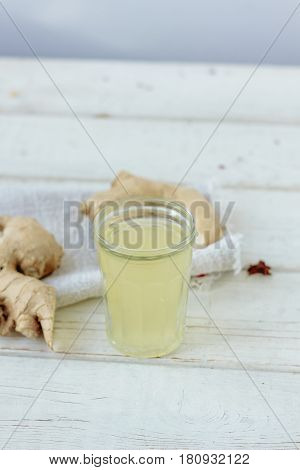 Ginger Juice In Small Glass Jar With Ginger Root Behind.