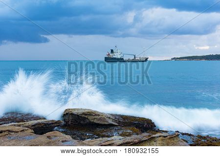 Big Wave Hitting The Rock With Barge On The Background