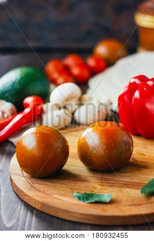 Kumato Tomatoes On Wooden Board Surrounded By Vegetables.