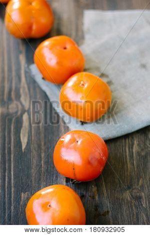 Line Of Persimmons On Wooden Table