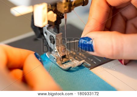 needlework and hand quilting in the workshop of a tailor - close-up on tailor fingers with a manicure stick the thread in the needle of the sewing machine. Hobby and sewing concept. poster