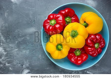 Red bell pepper and yellow bell pepper on plate top view