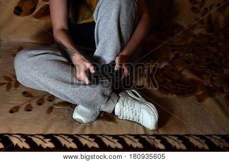 A Young Girl Plays Video Games With A Black Joystick With Many Buttons
