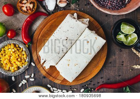 Vegetarian Burrito On Wooden Board Over Black Table Surrounded By Ingredients.