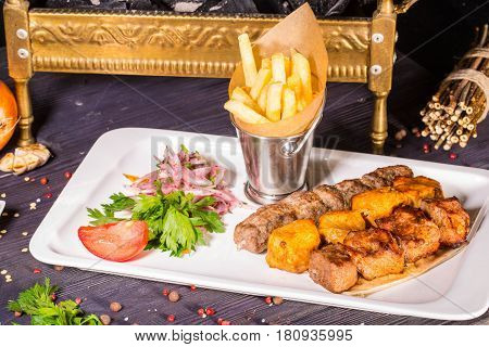 A shish kebab from chicken, a shish kebab from mutton and a shish kebab from veal, fried on coals