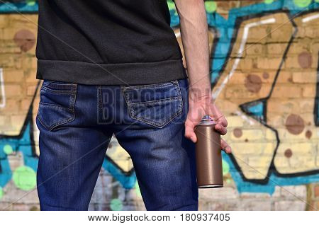 Graffiti Artist With A Spray Can In His Hand. Back View